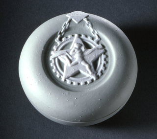 Flat, circular shape, of greenish bisque body. The top ornamented with an emblem of an athlete in raised contrasting white.
