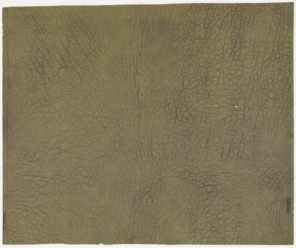 Textured green paper imitating embossed leather. Darker brown pigment rubbed into crevices.