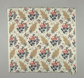 Reproduction-style fabric with alternate rows of oversized tan leaves with red and blue stipple pattern and leafy roses in shades of red and blue on a glazed off-white ground.