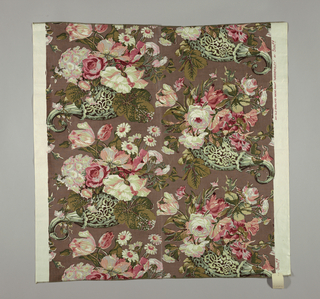 Reproduction-style fabric with a design of oversized flower motifs in pink, green and red on a brown ground.