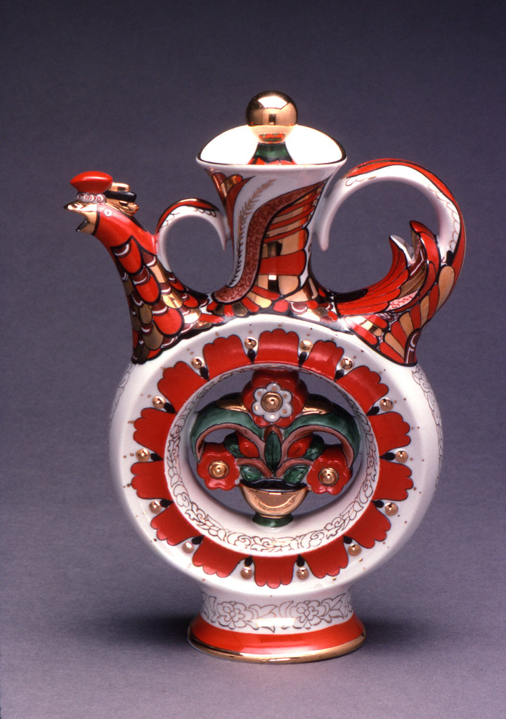 Circular body on tall, flared foot, long flaring neck, two loop handles, spout in the form of a bird's head; painted in bright orange, green, and gilding with folk motifs. Lid sits inside neck, has gilded ball finial.