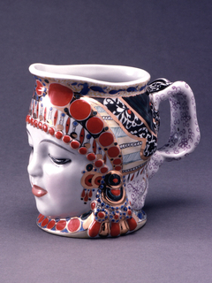Body in the shape of a woman's head wearing elaborate headdress, thick loop handle, slightly out-turned spout; richly patterned painted and gilt ornamentation.