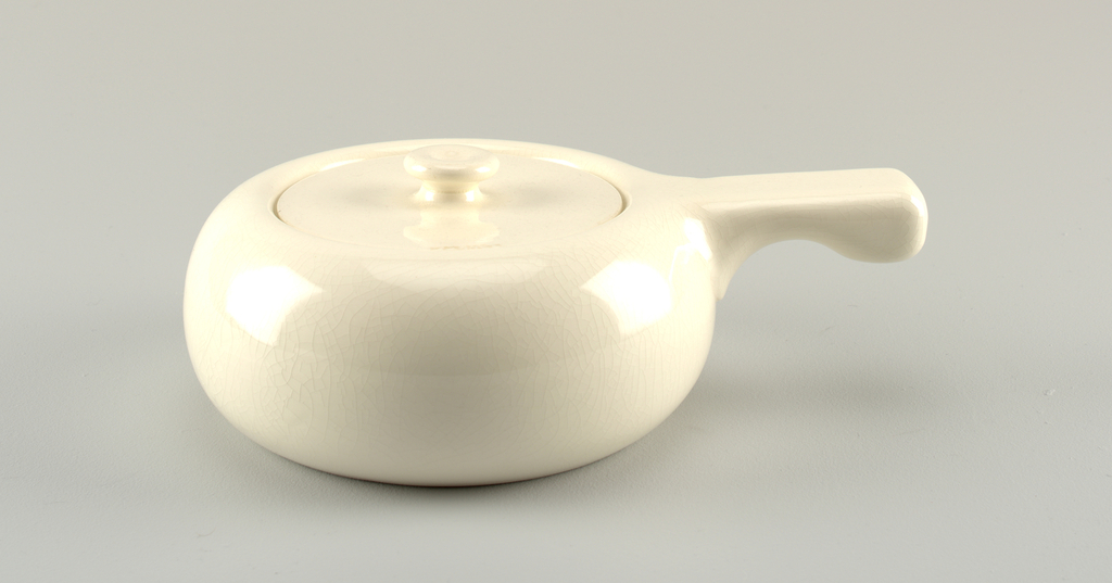 Round white pot with flush lid and button finial; pot has handle with straight top and curved bottom.