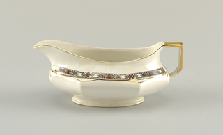 octagonal-sided gravy boat; cream colored ground with gilded details and poorly printed pattern in black and red around shoulder.
