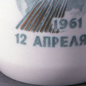 """Cylindrical, with loop handle; image of rocket, globe, inscription """"1961 / 12 April"""" (in Russian) on one side."""