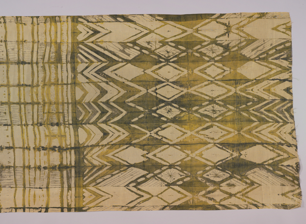 Wall hanging with all-over geometric pattern in greens and yellows.