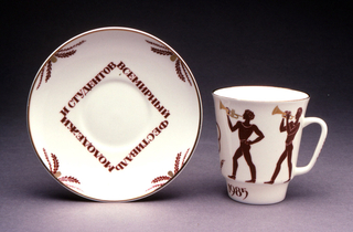 """Cup cylindrical, flaring towards top, narrowed at base, loop handle; painted in orange/brown with figures of young athletes blowing trumpets, emblem, """"1985"""" at base. Saucer circular; four sprays of leaves at border and inscription in square around center (in Russian): """"World Festival of Youth and Students"""" painted in orange/brown, gilded band at rim."""