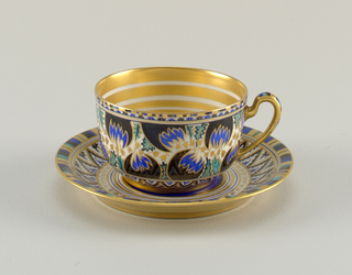 Decorated in conventionalized pattern in black, blue, green, gold on white background. Interior of cup shows concentric gilded lines. Stripes at saucer border.