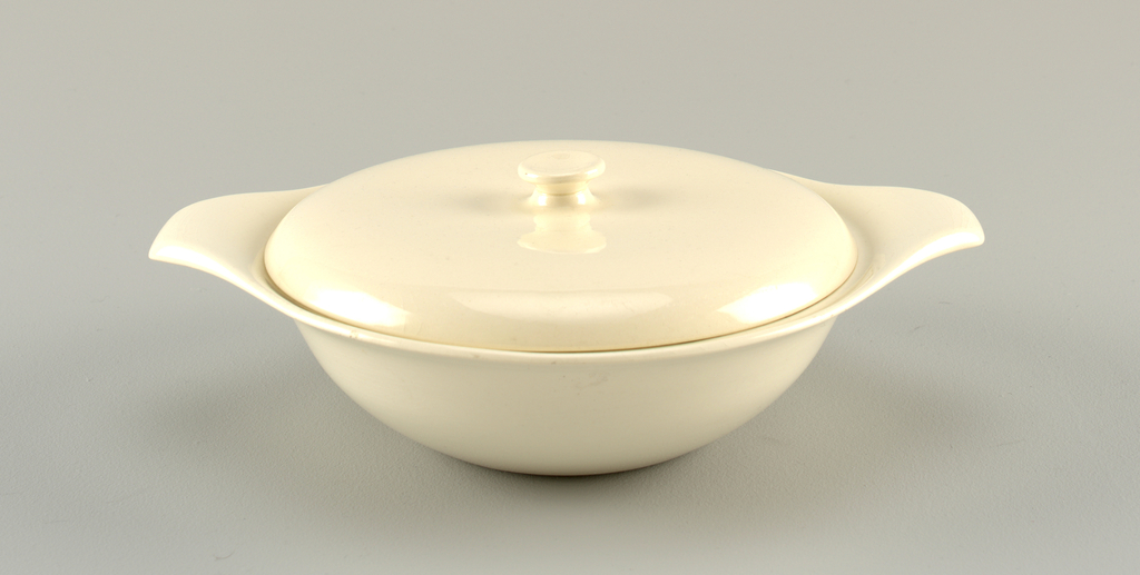 Round white dish with outturned handles and lid with button finial.