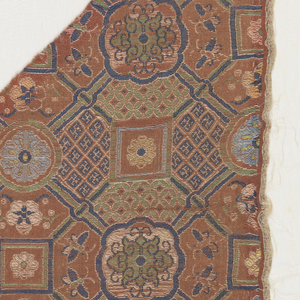Dark red-orange ground with a design formed by primary dark blue weft and secondary wefts of light and dark blue, green, pink, tan and yellow. Geometric design with minute lozenges and swastikas grouped into squares with rosettes in some areas of the design. Lotus medallions at intersections. With insects or butterflies. Right selvage present.