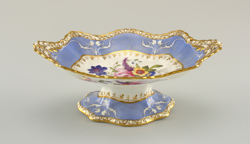 On oval foot a rectangular dish with deeply scalloped edge, the scallops on the short ends extended to form handles that are pierced by two holes on each. Decoration same as on 1959-155-1.