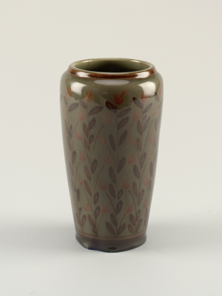 Grey-green ground with twelve underglaze vertical branches of brown leaves and muted red flowers. Tall, footless body, wider at shoulder than at base; vestigal neck, large mouth. Under-glaze brown bands at neck and base.