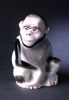 A monkey seated, looking over right shoulder; painted in browns and black enamel.