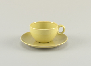 "Hemispherical cup (a) with thick circular loop handle; ""avocado"" yellow-green glaze.  Circular saucer (b) with raised edge as rim; ""avocado"" yellow-green glaze."