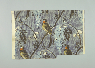 Multicolored block printed fabric with a shaded blue ground has black serpentine branches bearing blue grapes, small black leaves and perching black, yellow and red birds.