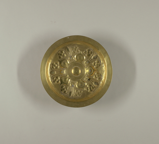 Deep round dish with narrow shallow rim; bottom decorated with repoussé design. About a small raised central boss surrounded by a band of illegible lettering, five onion-shaped petals spring outward, separating five lion masks facing outward from whose mouth spring three stems, the central stem terminating in a bunch of conventionalized grapes, the flanking ones terminating in a grape leaf and volute.