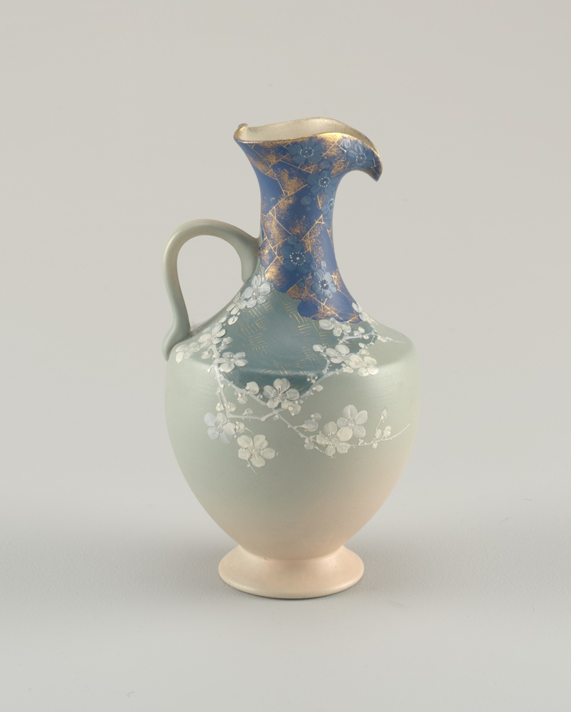 Thrown white stoneware body with applied handle, decorated with prunus blossoms and branches in white, enframing an overglaze-painted field of bright blue and gilded patterning. Upper portion of neck with field of Bristol blue and blue prunus blossoms against gilded patterning. Body painted in graduated tones from peach to pale celadon.