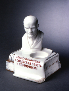 """In the form of two books, one sitting on top of the other, with a bust of Lenin resting on top; a scrolled paper-like form across the top and folding down the front side to form a pencil rest, inscribed (in Russian) """"Electrification + Soviet Power = Communism;"""" circular hole for inkwell on top. Inscription on binding of lower book on back side (in Russian): """"N. Lenin / (V. Ulyanov) / Volume X / Collected / Works."""" Inscription on top side of upper book (in Russian): """"Publishing House of the Sea Ministry""""[?"""