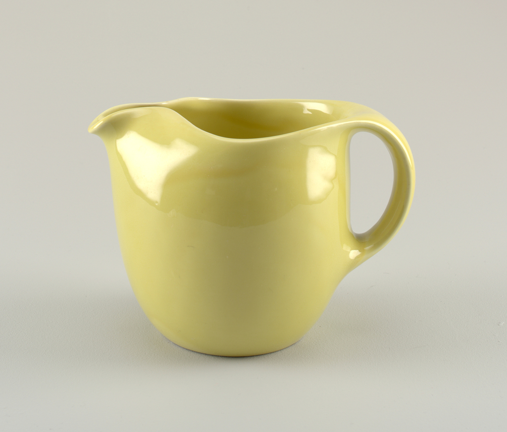 Body of cylindrical form tapering at base with large circular mouth with pinched spout and thick oval loop handle; yellow-green glaze.