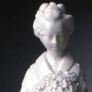 Woman dressed in Japanese costume holding bundle of flower blossoms; small circular base; unglazed.