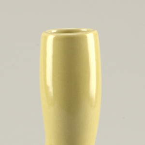 """Elongated globular body with protruding short spout at front.  Neck of carafe elongated forming slightly bulged cylindrical handle, open at top to permit filling.  Overall glaze of """"avocado yellow.""""  Unglazed ring at underside of base."""
