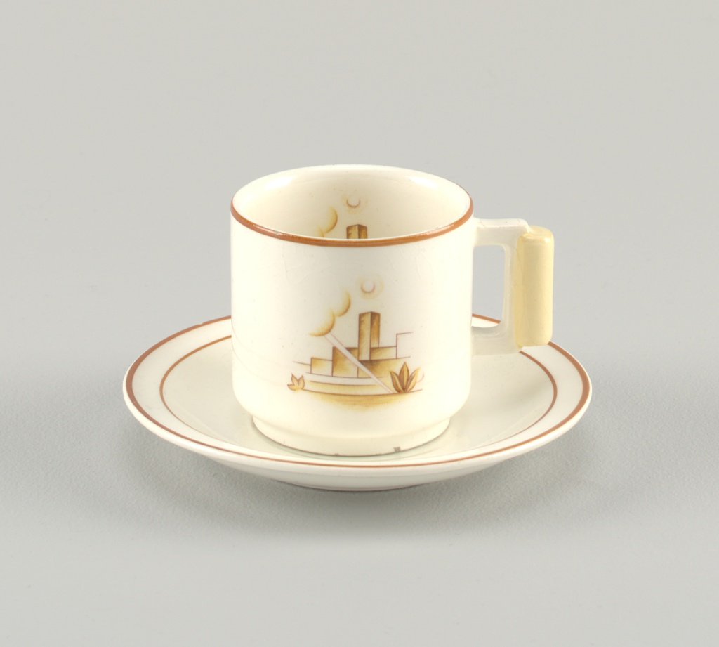 A white cup and saucer depicting an abstract outdoor scene. Image is on both inside and outside of cup. The saucer has brown stripes around the rim.