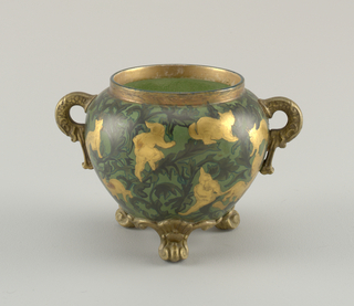 Footed bulbous jar in green with allover darker green leaf pattern, overlaid with gilt silhouetted cats and figures. Jar has scrolled and foliate feet; C-curved hands.