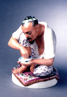 Man dressed in native costume, seated on left leg, right bent up at knee, he holds small bowl in left hand, right hand in bowl; circular base with oriental carpet on which he sits.