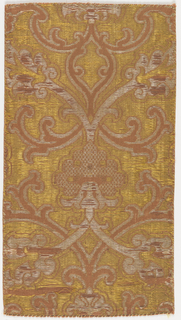 Symmetrical arabesques and a pomengranate motif filled with a checked diaper pattern. ln dark yellow and mauve.