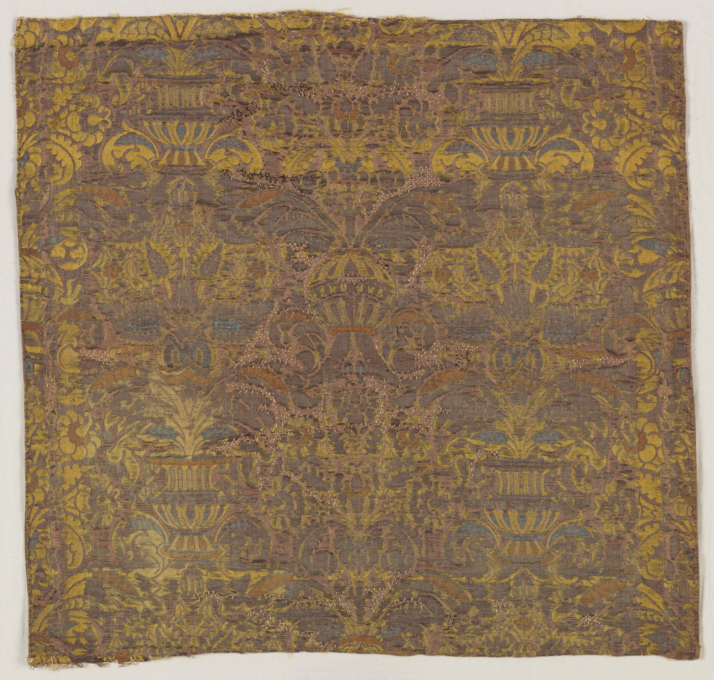 Symmetrical large scale floral motif derived from the pomegranate brocaded in light blue, yellow and brown on a mauve ground.