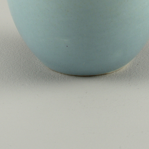 """Cylindrical slightly tapered form with thick circular loop handle; """"ice blue"""" glaze."""