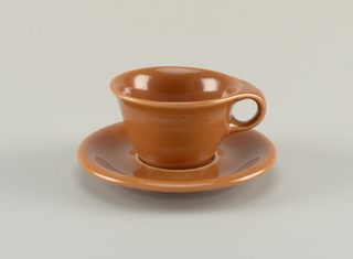 "Body of tapering circular form with flaring mouth and thick circular loop handle; ""nutmeg"" brown glaze."