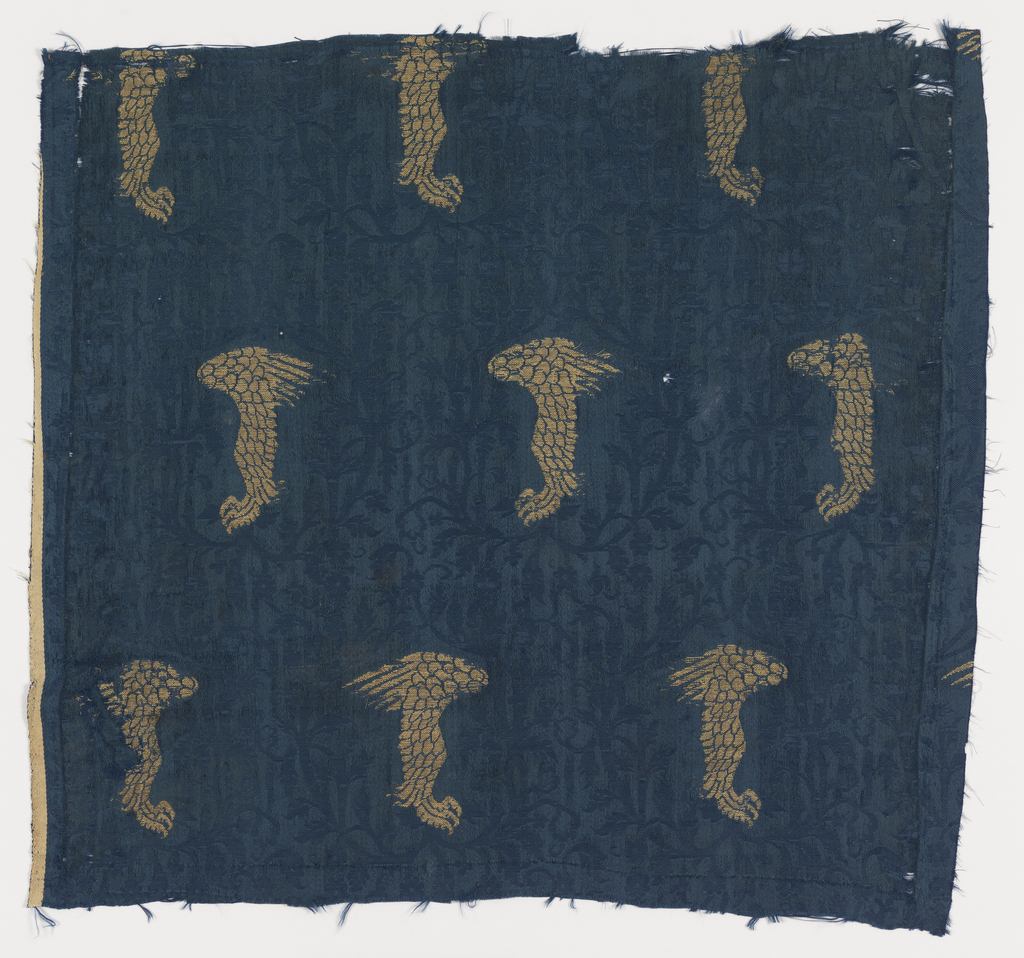 Dark blue fabric patterned with vines and brocaded with gold in a design of the leg of a strong bird.