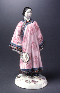 Woman dressed in Chinese robe, holding fan, standing on circular base with flower blossoms.
