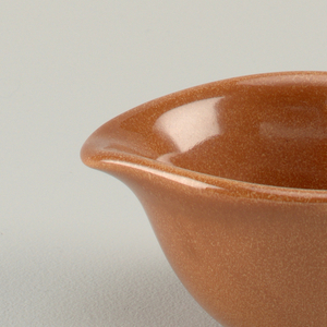 "Tapering globular body with flaring circular mouth, short pinched spout and open loop handle; ""nutmeg"" brown glaze."