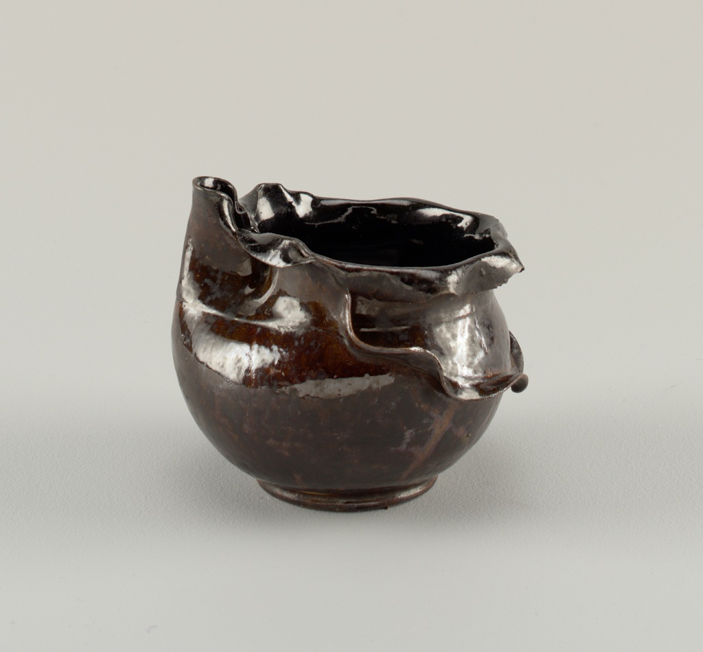 """Vase with spout. Red-buff colored clay body, thrown. Globular body with folded vertical spout, incised line demarcates shoulder, turned-down flat ruffled rim with jagged edges; low flat foot. Around back of body is applied ribbon-like ruffled """"apron."""" Exterior covered with variegated dark brown glaze mottled with darker splotches. Areas of exterior, particularly the lower half of body, have a dark film fired over the glaze. Interior covered with black glaze. Bottom partially glazed."""