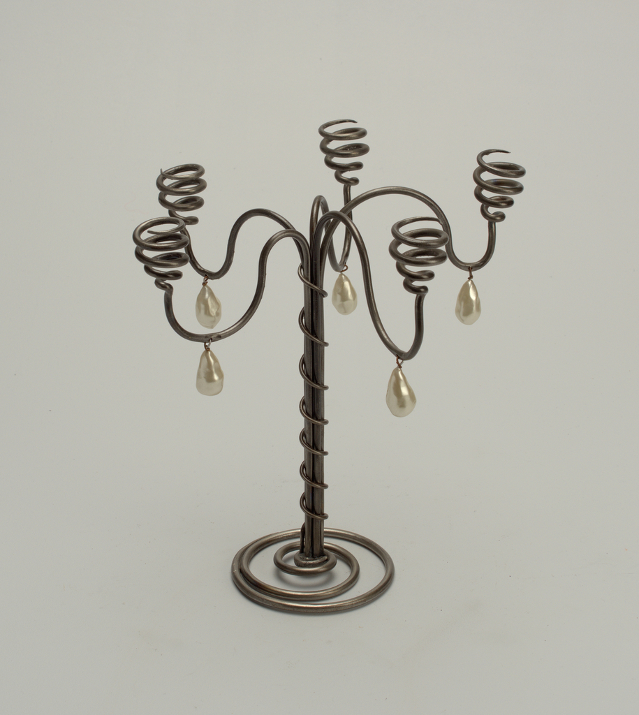 A five-branched candelabrum with scroll arms supporting coils to hold the candles, raised on bundled wire stem with serpentine coil descending into concentric spiral base.