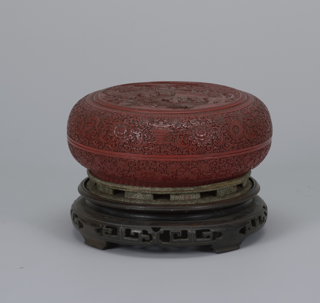 "Circular red lacquer box with short circular foot and fitted circular lid, sitting on carved wooden stand; foot carved with a fret or 'lei-wen"" pattern. Side of box carved with peony-like flowers interspersed with beribboned Buddhist-taoist symbols set among deeply carved buds and scrolls. Outside edge of lid carved with Eight Buddhist Emblems of Happy Augury interspersed among flowers and scrolls. Top of lid with carved landscape framed by a band of bud-like figures adjacent to inner band of interlocking geometric figures and ""shou"" characters."