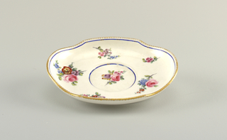 Oval form; upcurved rim with shaped edge; circular well; decoration of polychrome floral sprays, scalloped gilt band and blue band with gilt cross-strokes at rim; blue band around well.