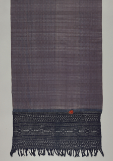 Long rectangular rebozo with narrow ikat stripes with dots and halves of diamonds alternating with a thinner stripe composed of two fine red stripes enclosing blue and white checked stripes. Warps on both ends are knotted to form an openwork border. Orange silk tassel attached to top of border at one end.