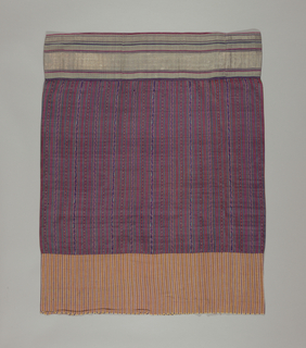 Three bands of various cloth weaves: plain cloth top border, plain cloth with weft ikat in center band, fancy compound cloth lower border. Wide stright tubular skirt made up of three horizontal bands hand sewn together: wide central band of fine silk cloth ikat-dyed to form narrow vertical stripes, some plain, some with zigzag or contorted dragon repeat in dark green, cerise, orange, black, purple, white, and turquoise. Bottom border has wide horizontal bands of silver fancy cloth and narrow guard stripes of cerise, purple, and green. top border (to be gathered in folds under sash0 is vertically striped with yellow and metal stripes alternating with narrower reddish-purple stripes in white borders. Cloth selvedge, cotton warps lower border. Raw edges on top border and plain selvedges top and bottom central band.