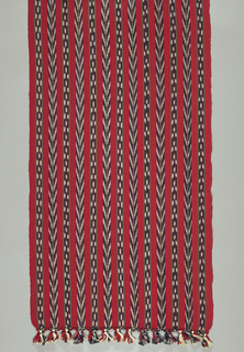 Long rectangular shawl with warp fringe, macramé beading and tassels at ends. Bright red with even stripes of dark blue and green jaspe patterns forming chevrons and other geometric shapes.