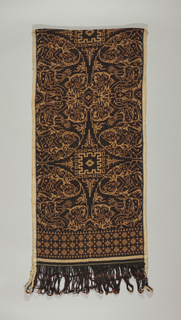 "Balinese textile known as a ""geringsing"" in dark brown, red and reserve white. Design is a symmetrical arrangement of half circles containing a seated figure. A narrow band of geometric patterning is at both ends. Tubular warp is uncut."