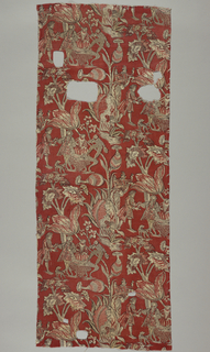 Red ground printed with a design of large flowering vine and blossoms with characters from the Comedie dell'Arte.