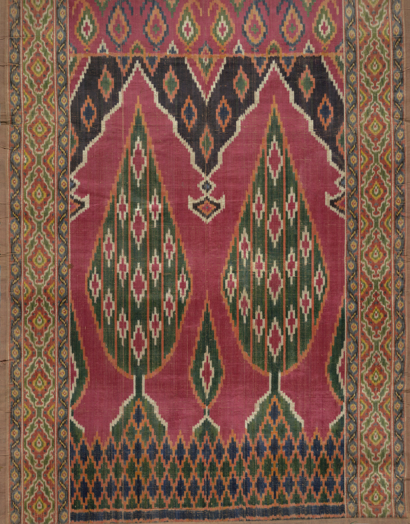 """Multicolored ikat velvet hanging with two cypress trees under pointed niches on a red background. Geometric boeder on both sides. """"Butah"""" patterned band at top."""