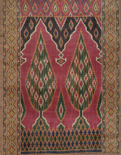 "Multicolored ikat velvet hanging with two cypress trees under pointed niches on a red background. Geometric boeder on both sides. ""Butah"" patterned band at top."