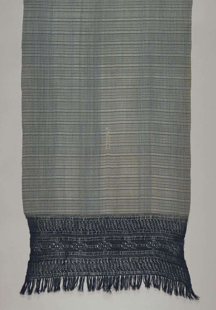 Between close-set narrow stripes, small geometric shapes make horizontal bands, all in indigo blue and white. Dark blue warp fringe, 15 inches deep in elaborate knotting, pattern of bands and rosettes.