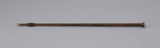 A dark wooden cane with a metal and cream colored end piece.