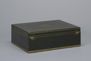 "Rectangular box (a) covered in dark green leather with stamped gilt bands and borders; hinged lid decorated with gilt borders and a cartouch comprising a crown surmounting flowing ribbons and drapery surrounding an eagle encircled by a chain of office(?) with the letter ""N"" in shield, and pendant medal.  Two hook closures at front.  Interior lined in tan suede and fabric, with wells for cabaret service pieces; rectangular suede cushion (b)."