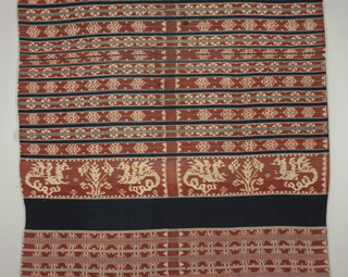 Cotton wrapper in a design showing, geometric patterning, plant-like forms and rosettes in red, blue, dark blue and off-white.
